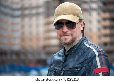 Man in the blue leather jacket, sunglasses, baseball cap