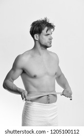 Man with blue measuring tape around naked torso. Guy with towel and flexible ruler isolated on white background. Athlete with serious face measures waist or sixpacks. Sports and weight loss concept