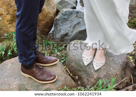 87b2a4cbaf a man in blue pants and brown shoes and a girl in a white wedding dress