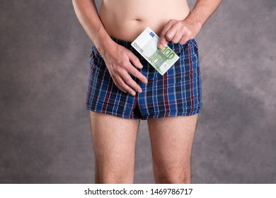 man in blue plaid boxer shorts with money in front of gray background