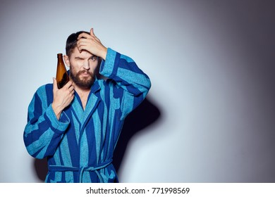 a man in a blue robe holds a bottle of beer on a gray background