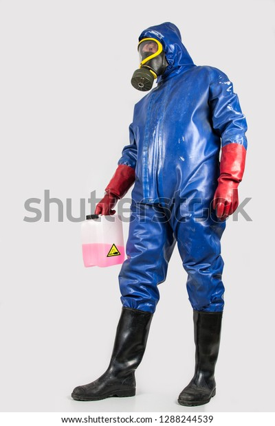 Man in blue rubber protective suit, with gas mask, red rubber gloves and black rubber boots holds a canister with a red and corrosive cleaning liquid in his  hand.