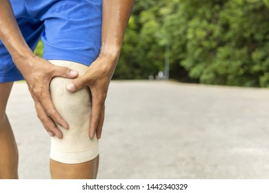 Man with blue runing shorts use hands hold on his knee after running on road in morning time with copy space for text or design