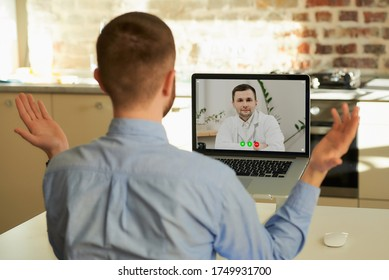 A man in a blue shirt at the doctor's appointment on a video call on his laptop computer at home. A guy gets a doctor's an online consultation to avoid the spread of coronavirus.