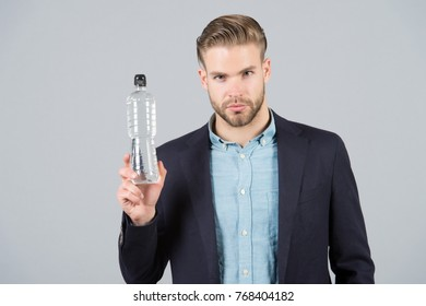 Man in blue shirt, black jacket hold bottle of water on grey background. Thirst, dehydration concept, health