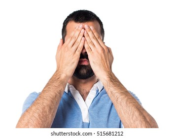 Man with blue shirt covering his eyes
