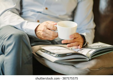 Man in a blue shirt with a cup of coffee, reading a magazine at home