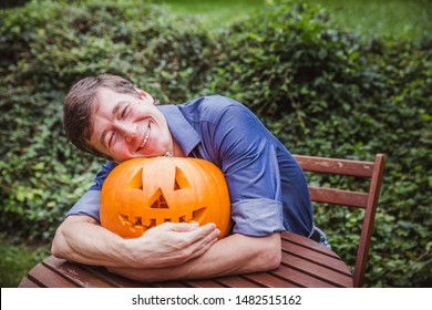 Man in blue shirt holding big pumpkin in front of his face. Happy Halloween