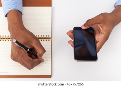 Man in blue shirt holding cellphone and writing in his notebook. Concept of office work and business. Top view