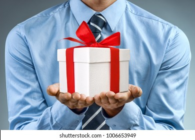 Man in blue shirt holding white gift box with red ribbon. Close up. Business concept