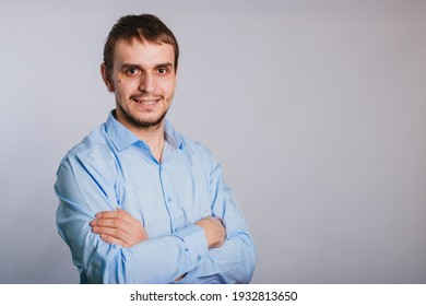Man in a blue shirt on a white background office worker. A guy with a cute smile