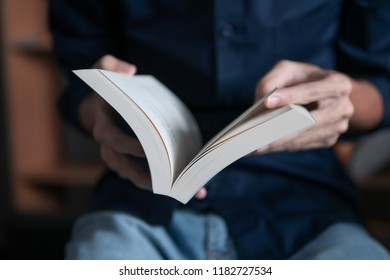 Man in blue shirt reading a book