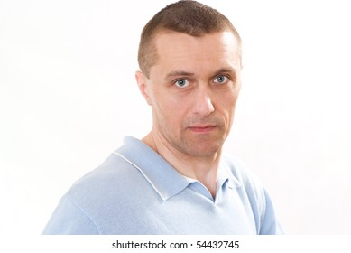 man in a blue shirt standing on a white