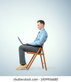 Man in a blue shirt with a tie sits on a chair working with a laptop.