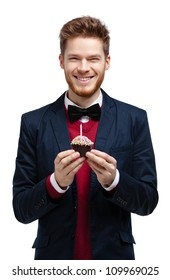 Man in blue suit with bow tie holds small tart, isolated on white