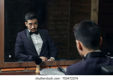 man in blue suit and butterfly sitting in chair looking in the mirror in barbershop.