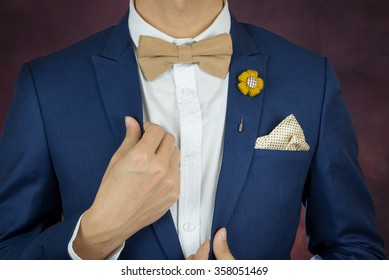 Man in blue suit with coffee cream bowtie color, flower brooch, and dot pattern handkerchief, close up