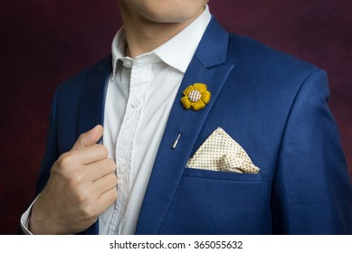 Man in blue suit with  flower brooch, and dot pattern handkerchief, close up