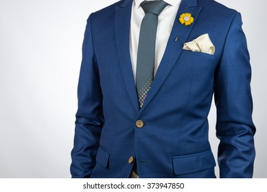 Man in blue suit with grey necktie, flower brooch, and dot pattern pocket square, white background