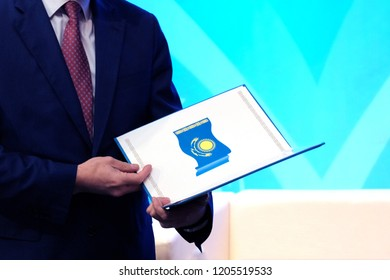 A man in a blue suit holds an open folder with the image of the national flag of the Republic of Kazakhstan. The concept of awarding a civil servant. Copy space.