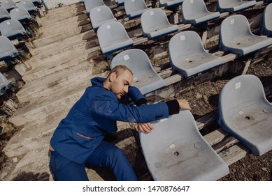 Man in blue suit sleeping after hard work cycle on fan tribune on stadium