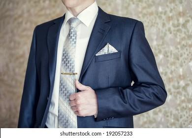 Man in blue suit with tie, tie clip and handkerchief