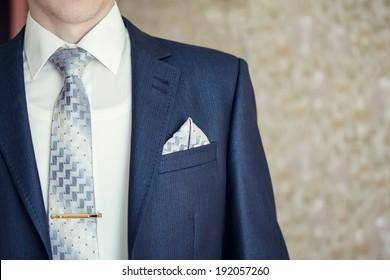 Man in blue suit with tie, tie clip and handkerchief. Focused on handkerchief