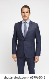 man with blue suit and a tie with patterns