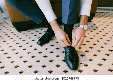 Man in a blue suit wearing a black shoe on