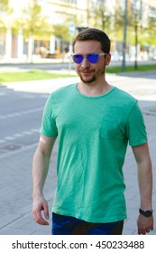 Man in blue sunglasses and green t-shirt walks along the street
