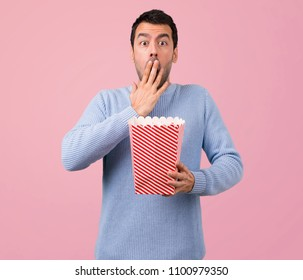 Man with blue sweater eating popcorns on pink background