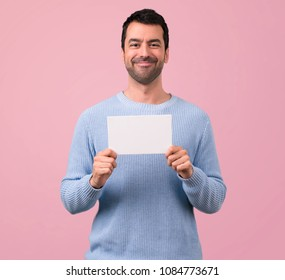 Man with blue sweater holding an empty white placard for insert a concept on pink background