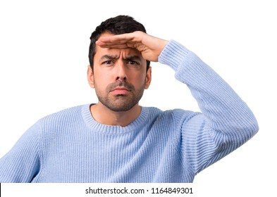 Man with blue sweater looking far away with hand to look something