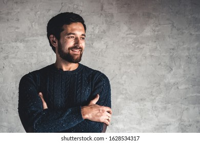 A man in a blue sweater on a gray background.