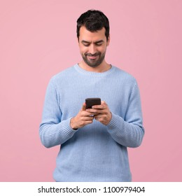 Man with blue sweater using mobile phone on pink background
