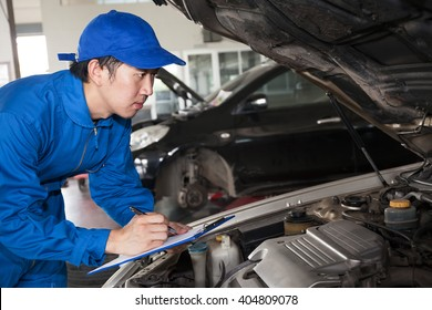 Man in blue technician uniform going to repair for car maintenance.