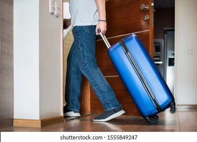 man with blue trolley luggage leavin the house