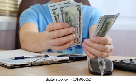 Man in blue T-shirt counting dollars and filling tax form. He calculating expenses and writing on tax document