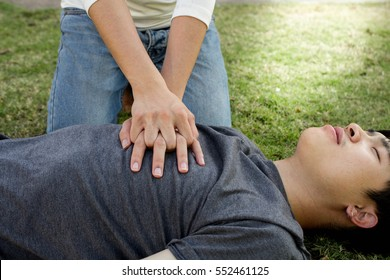 man with blue t-shirt lay down and man with white Long-sleeved shirt trains CPR on the grass black ground / concept In the process of resuscitation (first aid) ,RESCUE CPR TRAINING TO SAFE LIFE