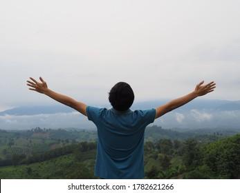 青いTシャツを着た男が腕を上げて空を見た。