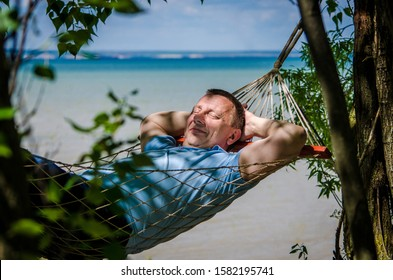 A man in a blue t-shirt swings in a hammock on beach, smiles in shade of trees. Vacation on a tropical island. The concept of relaxation, pleasure, pleasant bliss while traveling.