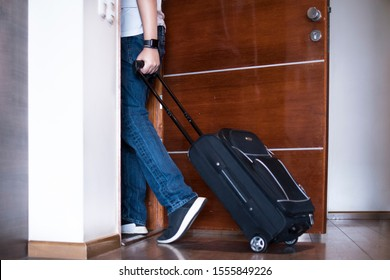 man in bluejeans, white t-shirt and watch leaving house with black trolley luggage. Walking through a wooden door.