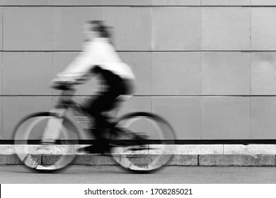 A man in blurry focus is riding a fast Bicycle against a static black-and-white wall. Athletic girl engaged in Cycling