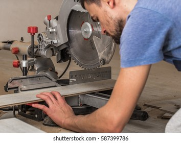 a man with a Board and miter saw closeup, concept building and repair