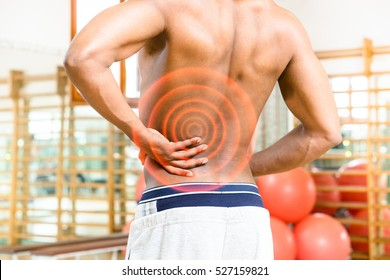Man body with aching back rear view with red circles expressing pain and fitness center background - Shirtless african guy touching his painful hip inside gym - Medical concept of workout risks