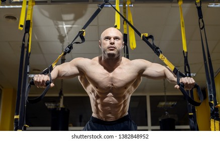 Man bodybuilder perform exercise with TRX in GYM