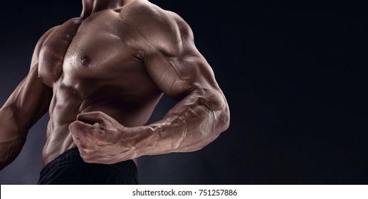 man bodybuilder showing muscular body over black background