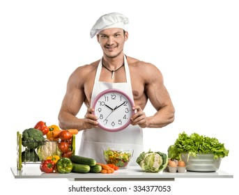 Man bodybuilder in white toque blanche and cook protective apron, hold on hands clock , on whie background, isolated