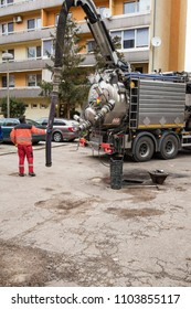 Man in boilersuit is pumping sewage with drainage suction sewage truck