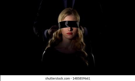 Man bonding female eyes with black ribbon, sexual slavery concept, women rights